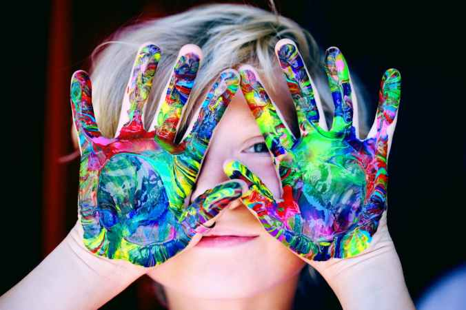 A young child holds their hands in front of their face, peering through fingers. Their hands are covered in bright paints.