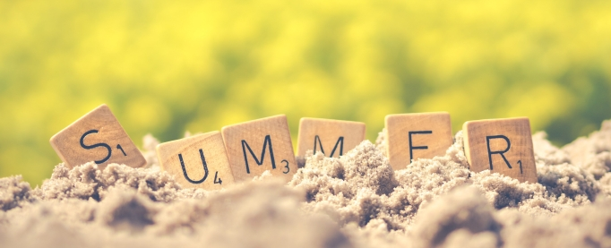 'Summer' written with Scrabble tiles in the sand