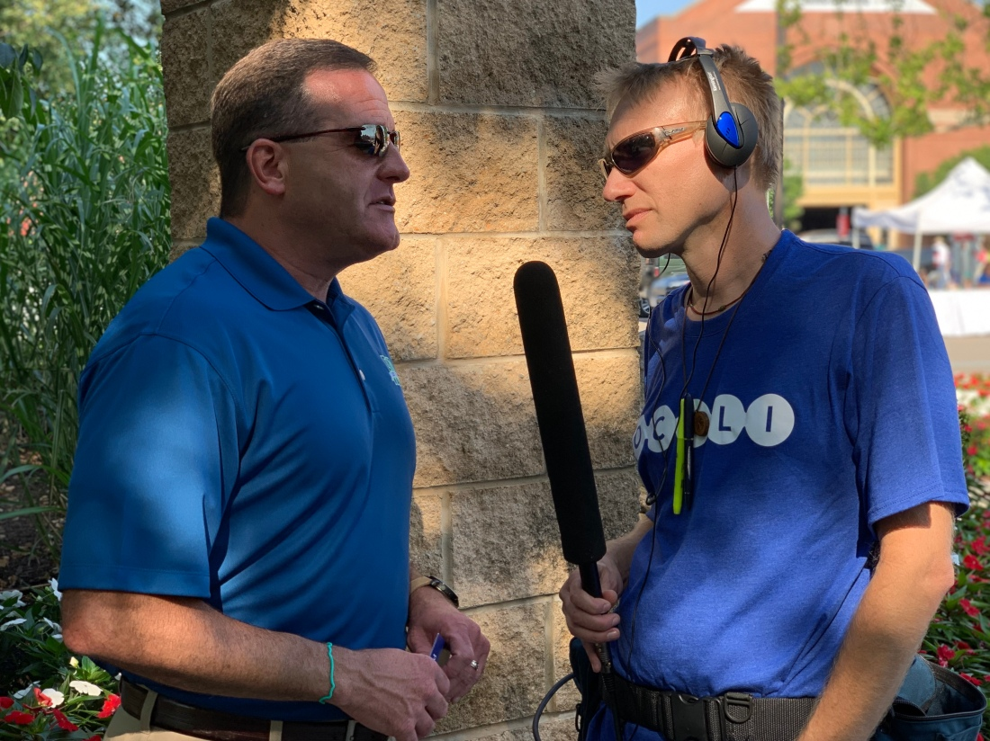 Man with large microphone interviewing man