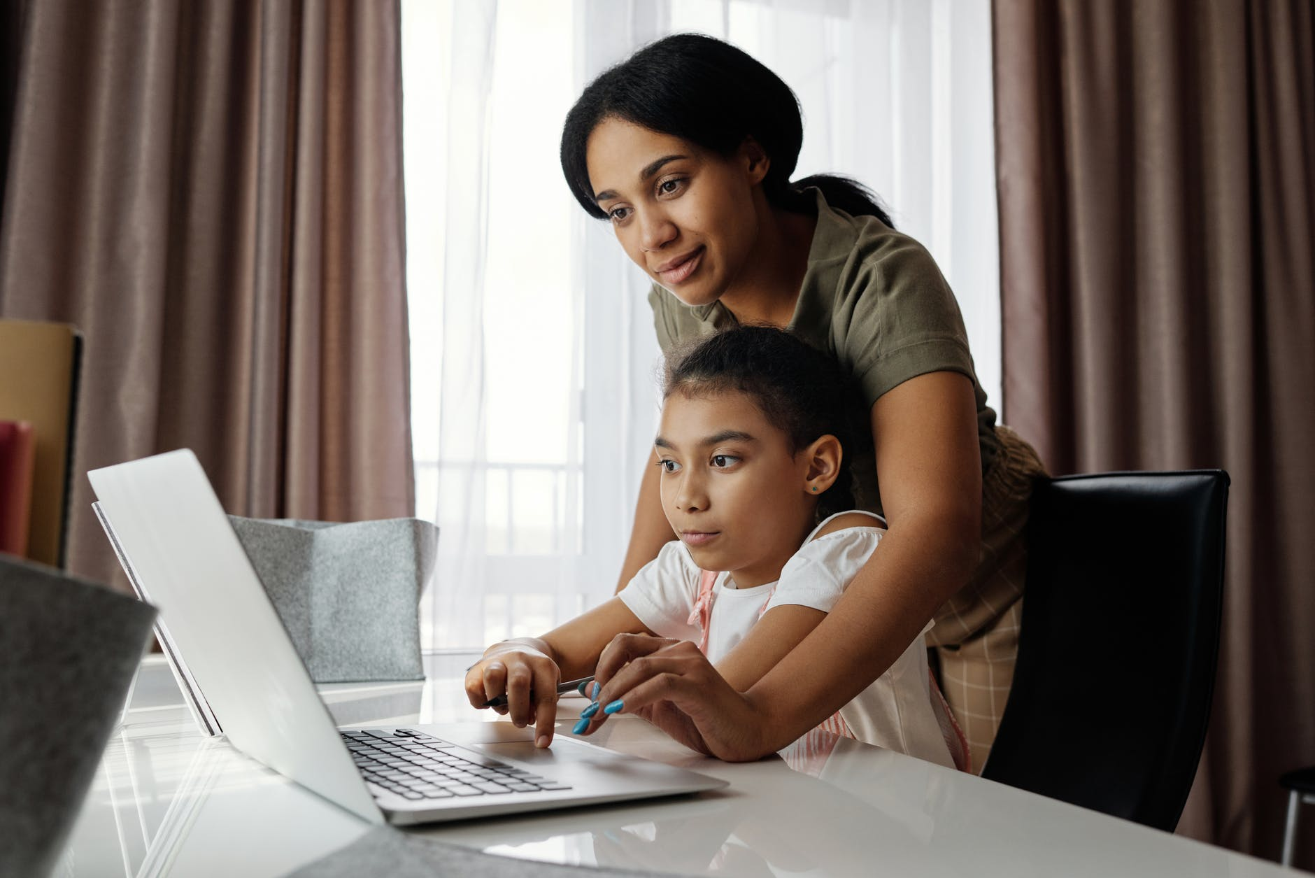 Mom assists daughter with work on laptop computer
