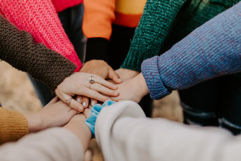 A group of hands meeting together in the middle